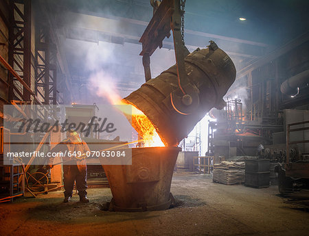 Steel worker and buckets of molten metal in steel foundry Stock Photo - Premium Royalty-Free, Image code: 649-07063084