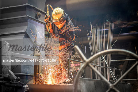 Man in protective clothing at work in steel foundry Stock Photo - Premium Royalty-Free, Image code: 649-07063086