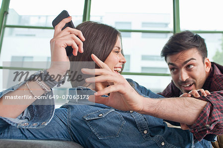 Young couple at home fooling about with mobile phone Stock Photo - Premium Royalty-Free, Image code: 649-07063173