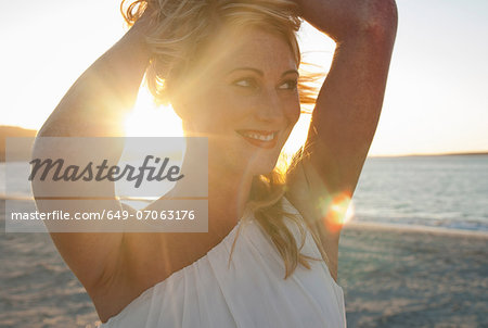 Close up of blond woman on beach at dusk, Cape Town, South Africa