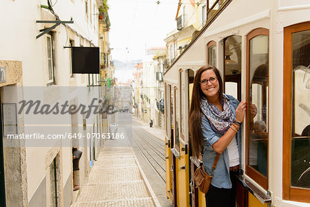 Portrait of young female tourist riding tram in Lisbon, Portugal Stock Photo - Premium Royalty-Free, Image code: 649-07063186