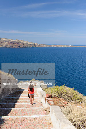 Female tourist walking down steps, Oia, Santorini, Greece