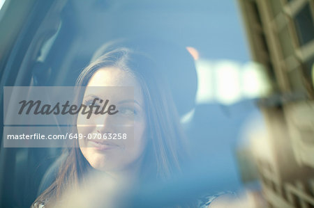 Young woman looking out of car window Stock Photo - Premium Royalty-Free, Image code: 649-07063258
