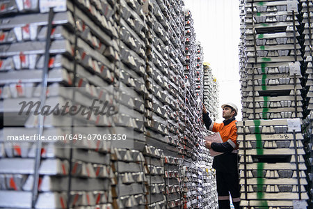 Warehouse worker checking stacked aluminum ingots Stock Photo - Premium Royalty-Free, Image code: 649-07063350