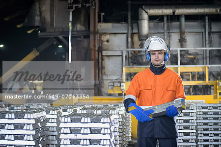 Portrait of warehouse worker holding aluminum ingot Stock Photo - Premium Royalty-Free, Image code: 649-07063354