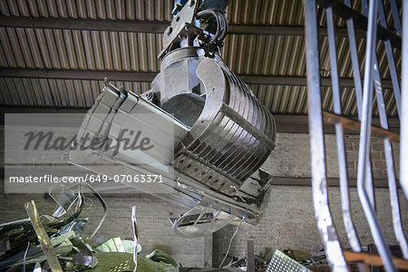 Excavator lifting scrap metal in warehouse Stock Photo - Premium Royalty-Free, Image code: 649-07063371
