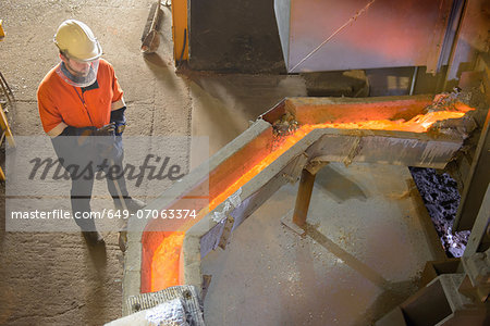 Worker monitoring molten metal at aluminum recycling plant Stock Photo - Premium Royalty-Free, Image code: 649-07063374