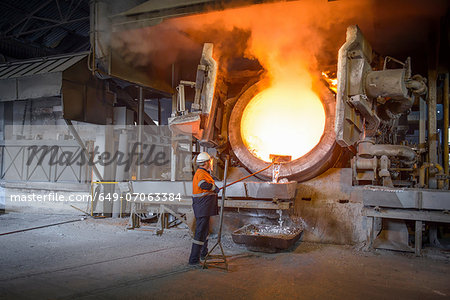 Worker raking liquid aluminum from furnace at recycling plant Stock Photo - Premium Royalty-Free, Image code: 649-07063384