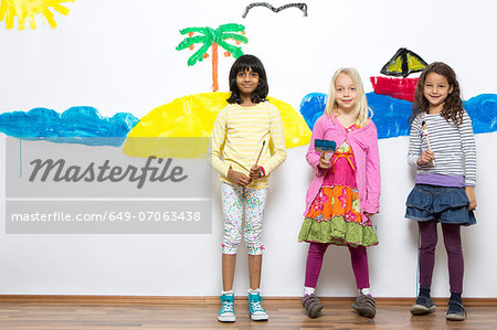Three girls in front of ocean and island wall painting Stock Photo - Premium Royalty-Free, Image code: 649-07063438