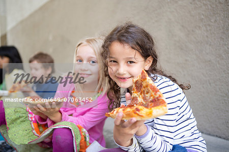 Small group of children eating pizza outdoors Stock Photo - Premium Royalty-Free, Image code: 649-07063452
