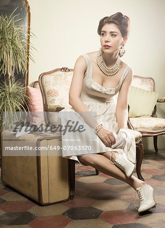 Woman in vintage clothes waiting in lobby with suitcase Stock Photo - Premium Royalty-Free, Image code: 649-07063570