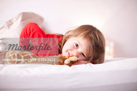 Young girl lying on bed with toy giraffe Stock Photo - Premium Royalty-Free, Image code: 649-07063622