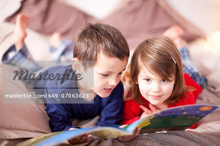 Two young children lying on bed looking at picture book Stock Photo - Premium Royalty-Free, Image code: 649-07063623