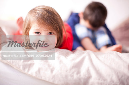 Portrait of young girl smiling and brother sulking Stock Photo - Premium Royalty-Free, Image code: 649-07063624