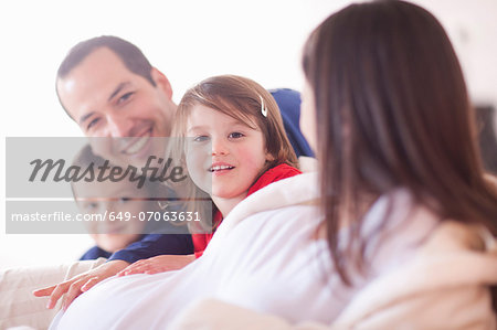 Parents and young two children lounging on bed Stock Photo - Premium Royalty-Free, Image code: 649-07063631