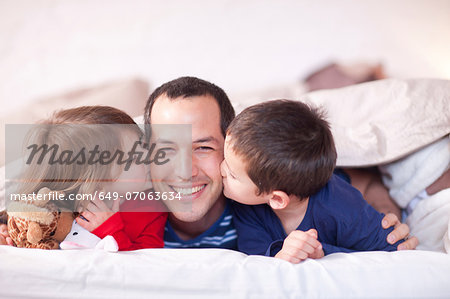 Son and daughter kissing fathers cheek under duvet Stock Photo - Premium Royalty-Free, Image code: 649-07063634