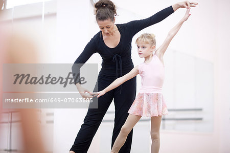 Young ballerina practicing pose with teacher Stock Photo - Premium Royalty-Free, Image code: 649-07063685
