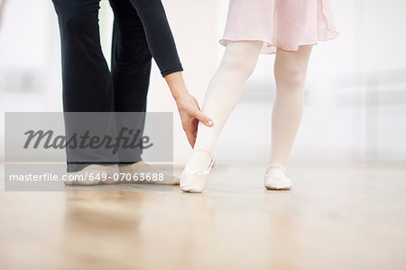 Close up of a young ballerina and teacher practicing toe point Stock Photo - Premium Royalty-Free, Image code: 649-07063688