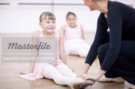 Teacher adjusting feet position of young ballerina Stock Photo - Premium Royalty-Free, Image code: 649-07063694