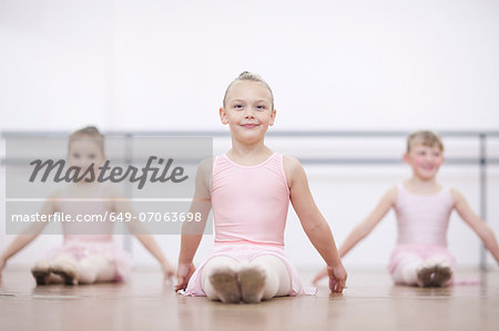 Young ballerinas in pose whilst sitting on floor Stock Photo - Premium Royalty-Free, Image code: 649-07063698