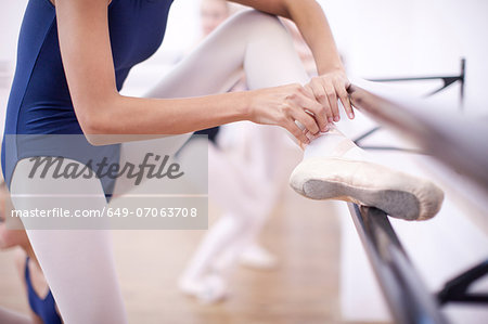 Ballerina fastening ballet slipper at the barre Stock Photo - Premium Royalty-Free, Image code: 649-07063708