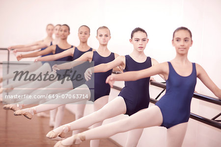 Row of teenage ballerinas with legs outstretched Stock Photo - Premium Royalty-Free, Image code: 649-07063714