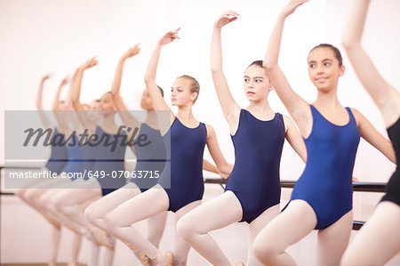 Row of teenage ballerinas with arms outstretched Stock Photo - Premium Royalty-Free, Image code: 649-07063715