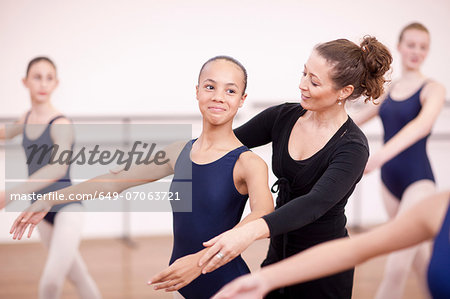 Teacher adjusting arms of shy teenage ballerina Stock Photo - Premium Royalty-Free, Image code: 649-07063721