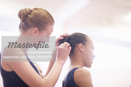 Teenage ballerina helping friend with hair Stock Photo - Premium Royalty-Free, Image code: 649-07063731