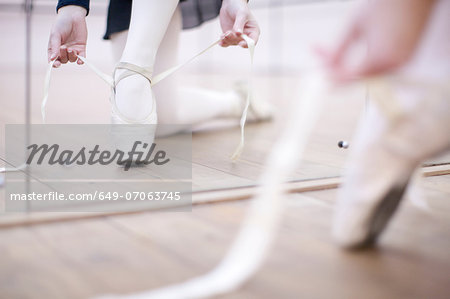 Ballerina putting on ballet slippers Stock Photo - Premium Royalty-Free, Image code: 649-07063745