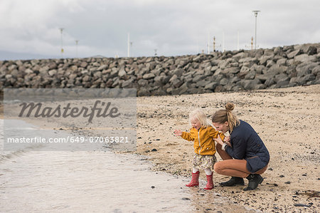 Mother and toddler crouching at waters edge Stock Photo - Premium Royalty-Free, Image code: 649-07063821