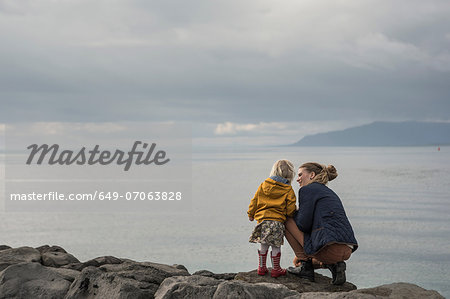 Mother and toddler crouching on harbor wall Stock Photo - Premium Royalty-Free, Image code: 649-07063828