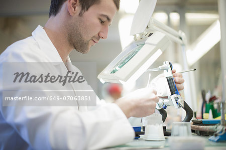 Dental technician using magnifier to repair denture Stock Photo - Premium Royalty-Free, Image code: 649-07063851