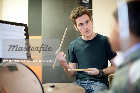 Young male teaching boy how to play drum kit Stock Photo - Premium Royalty-Free, Image code: 649-07063862