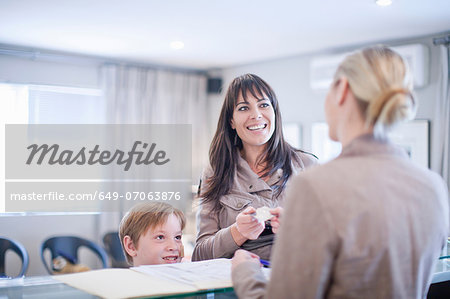 Mother and son making appointment at hospital reception Stock Photo - Premium Royalty-Free, Image code: 649-07063876