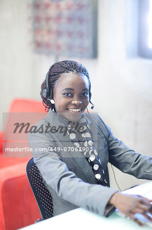 Young woman using telephone headset in office Stock Photo - Premium Royalty-Free, Image code: 649-07063903