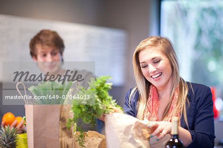 Young couple unpacking groceries Stock Photo - Premium Royalty-Free, Image code: 649-07064013