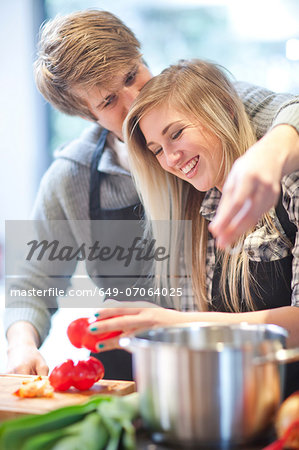 Affectionate young couple preparing meal Stock Photo - Premium Royalty-Free, Image code: 649-07064025