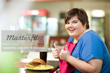 Young woman in cafe with unhealthy meal Stock Photo - Premium Royalty-Free, Image code: 649-07064043