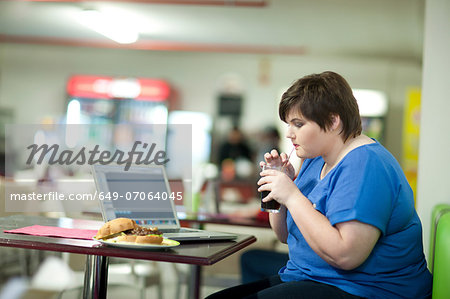 Young woman drinking coke in cafe Stock Photo - Premium Royalty-Free, Image code: 649-07064045