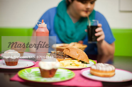 Young woman in cafe with table of food Stock Photo - Premium Royalty-Free, Image code: 649-07064049