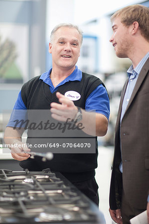 Young man negotiating with salesman in showroom Stock Photo - Premium Royalty-Free, Image code: 649-07064070