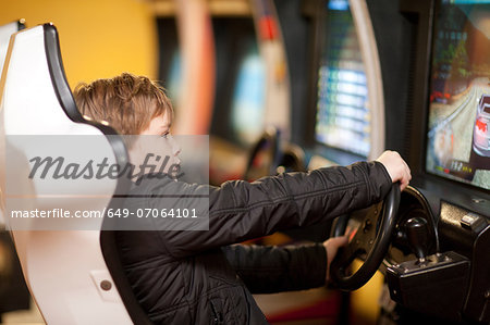 Boy playing on driving video game Stock Photo - Premium Royalty-Free, Image code: 649-07064101