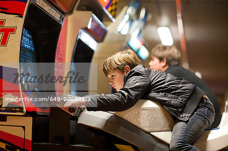 Two young brothers playing on driving video games Stock Photo - Premium Royalty-Free, Image code: 649-07064112