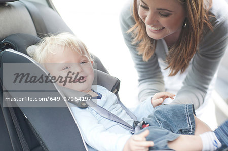 Mother checking baby son in back seat of car Stock Photo - Premium Royalty-Free, Image code: 649-07064197
