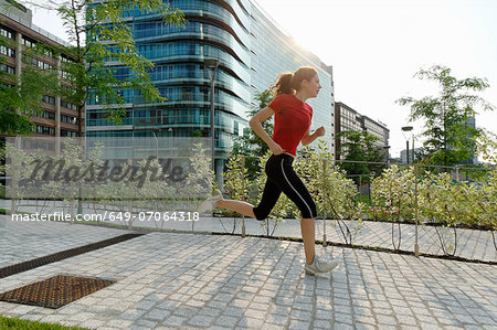 Young woman running past office buildings Stock Photo - Premium Royalty-Free, Image code: 649-07064318