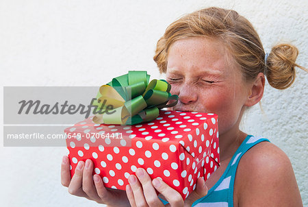 Girl kissing gift in hand Stock Photo - Premium Royalty-Free, Image code: 649-07064411