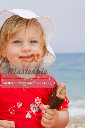 Baby girl eating ice cream on beach Stock Photo - Premium Royalty-Free, Image code: 649-07064520