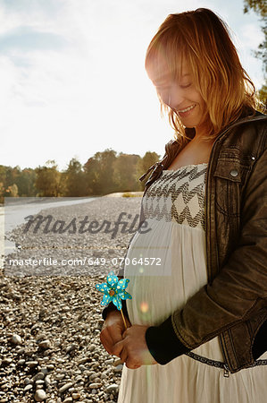 Pregnant woman standing beside river holding windmill Stock Photo - Premium Royalty-Free, Image code: 649-07064572