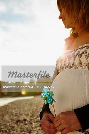 Pregnant woman standing beside river holding windmill Stock Photo - Premium Royalty-Free, Image code: 649-07064573